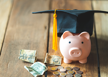 A piggy bank wears a graduation cap with money in front of it