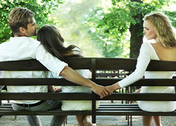 Man Holding Woman on Bench While Holding Hands with Another Woman