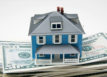 A miniature house sitting on a stack of money