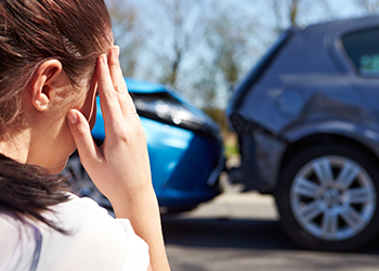 Woman holds her head next to a car accident