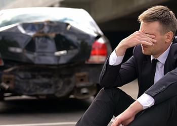 Man sits rubbing his eyes next to crashed car