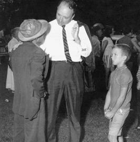 Eight-year-old Mike listens intently to his father console the father of a young man that Boyce had sent to prison as District Attorney
