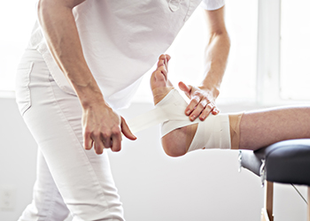 A doctor is touching an ankle wrapped in bandages