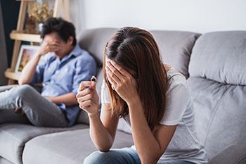 Frustrated couple on the couch reconsidering marriage