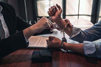 Attorney unlocking man's handcuffs