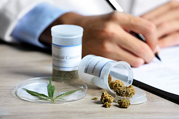 Medical Marijuana resting on a doctor's desk as he writes a perscription
