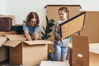 2 young girls helping unpack moving boxes