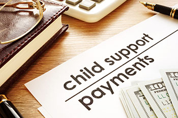 Child Support Payments documents with money on top