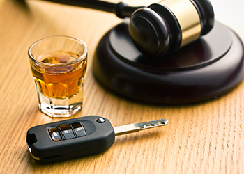 A shot glass, a car key, and a gavel are on a table