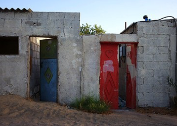 A run down stone structure with a bule door and a red door