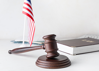 A gavel, a small American flag, and a law book rest on a white backdrop