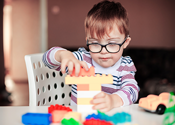 A little boy in glasses plays with lego blocks