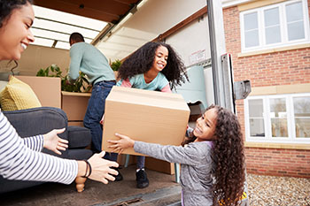 Two children helping their mother get boxes out of a moving truck