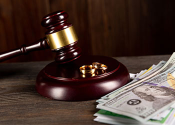 gavel next to rings and stack of money