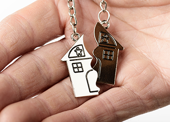 A person holds two halves of a house shaped key chain