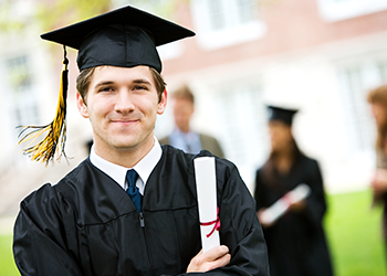 A college graduate poses in his gown and hat with his diploma