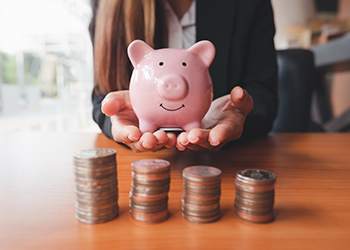 A woman holds a pink piggy bank