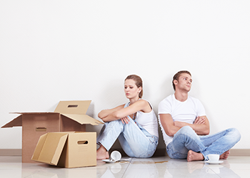 A frustrated couple sits near empty moving boxes