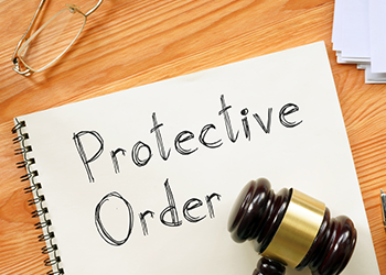 Protective Order writen on a notebook next to a gavel