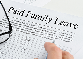 A person fills out a Paid Family Leave form