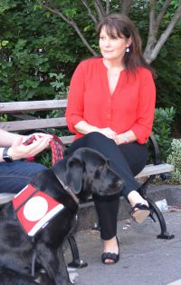 Sue Palmer sitting with a client and his service dog