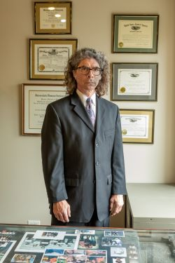 Attorney John Culver behind a desk and in front of diplomas