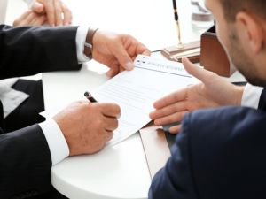 Man pointing to paper as another person signs it