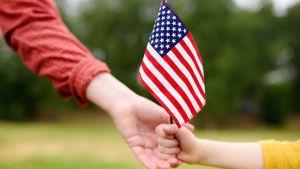 Child handing adult American flag