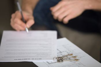 Person signing a document with three keys on top