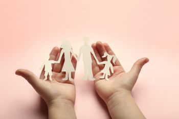Paper family in child hands on pink background