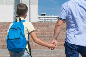 Dad is leading a boy with a backpack to school