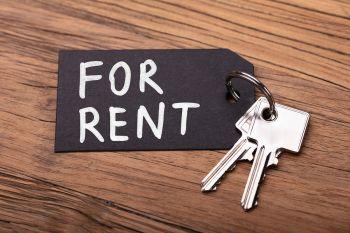 """Keys on a desk labeled """"For Rent"""""""