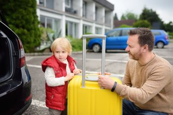 Father and son putting a suitcase in their car trunk