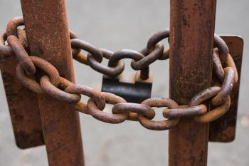Rusted chain around two metal bars