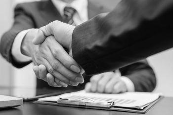 Business men shaking hands over paperwork