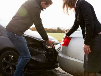 Two people checking their cars after a fender bender