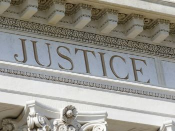 Justice written on top of a courthouse column
