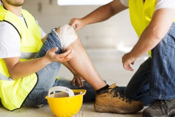 Construction worker down on the ground with a wrapped knee