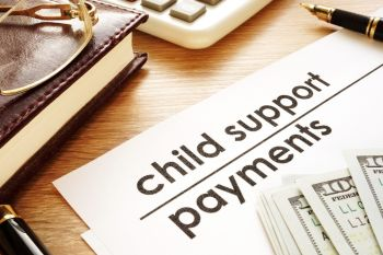 Child support payment document with money resting on top of it