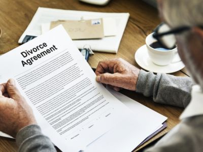Man with glasses looking over a divorce agreement