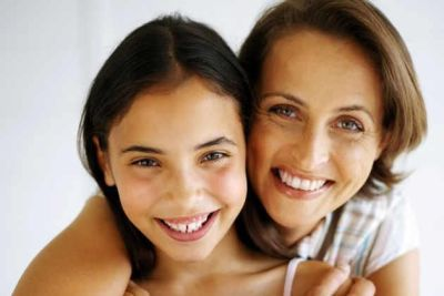 Smiling mother holding her happy daughter