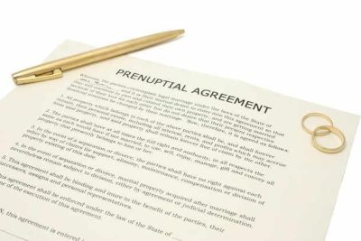 Prenuptial agreement with a pen and two rings on top