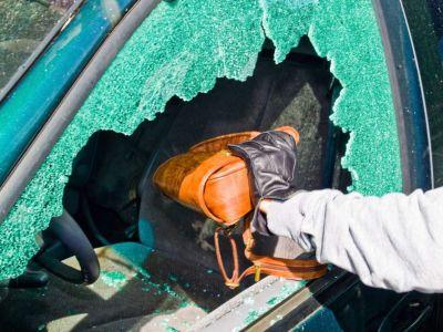 Person reaching through broken window to grab a bag