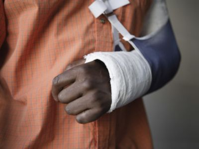 Person wearing orange shirt with arm in a cast and sling