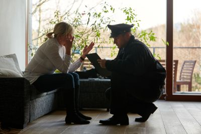 visibly upset woman sitting on couch talking to a police officer