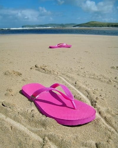 pink flip flops spread out in sand on a beach