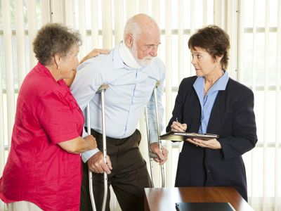 Elderly woman touching the shoulder and arm of an elderly man on crutches while talking to a woman in a suit holding a clipboard and pen