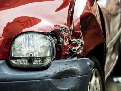 Close up of a headlight and a bumper damaged on a red car