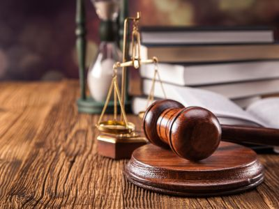 Gavel on table with scales of justice, stack of books, and hourglass