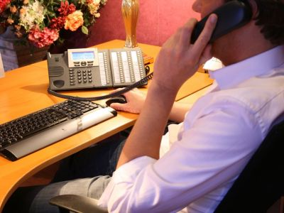 Man on the phone with hand on a mouse sitting at desk with keyboard